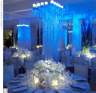 Jessika and Michael&#39;s reception area looks like a spectacular winter wonderland. Dripping icy chandeliers and lush, white centerpieces lit from below combine to create a wow-inducing scene awash in icy blue lighting.