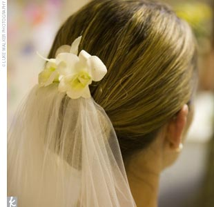 Sarah wore a low, simple hairstyle and tucked in two gardenias just above the veil.