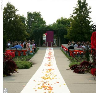 The ceremony took place at sunset in the Michigan State University Horticulture Gardens. Rows of white chairs, decorated with alternating fuchsia and tangerine sashes, were set up for guests. Amy and her bridal party walked down a white aisle runner splashed with orange, pink, and yellow rose petals and sidelined with shepherd's hooks holding? hang ...