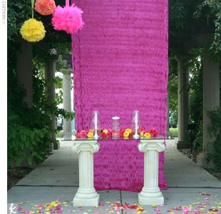 Because a parking lot was visible from the ceremony space, Amy had her florist drape fuchsia fabric behind the unity candle table. Three hanging pomanders also decorated the area.