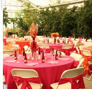 Tables set with floor-length fuchsia and tangerine linens filled the greenhouse at the horticulture garden. Trees lit with white lights lined the greenhouse, and fuchsia chiffon and votives adorned the cake table.