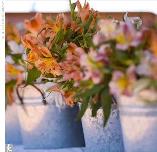 """Our decorations were simple, yet perfectly fit our surroundings,"" Kasey says. Silver buckets filled with orange and white alstroemeria sat atop brown linens, with votive candles adding a little glow."