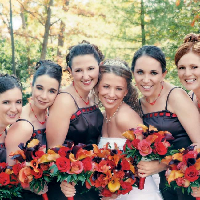 Laura held a round bouquet featuring calla lilies of rusty orange and dark burgundy, dusty orange Leonidas roses, and red Charlotte roses, all punctuated with Swarovski crystals. The bridesmaids wore full-length cognac-colored dresses accented with red ribbon. The ribbons on their dresses matched the ribbons that wrapped around their bouquets.