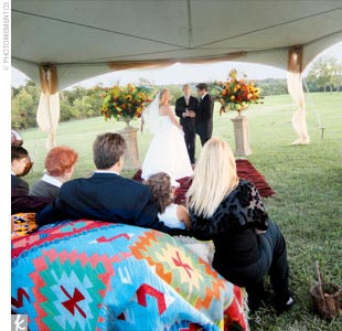 Stacy and Bert hosted their rustic wedding at their 1400-acre ranch just north of Kansas City. Two tents were set up for the ceremony and the reception. During the ceremony, guests sat on hay bales covered in antique oriental rugs, and two large flower arrangements were set up on each side of the tent in antique urns.
