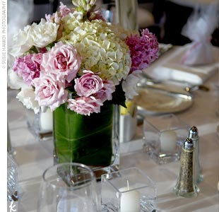 Round tables were covered with white linens and topped with square vases containing pink and white roses with internally wrapped green leaves. White candles, scattered across each table, cast a romantic glow.