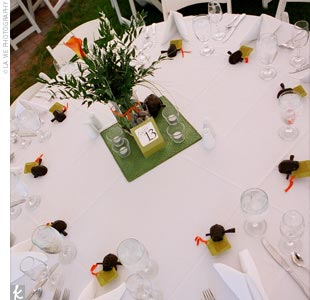 The centerpieces were designed by none other than Cara herself (though placed by her florist), and included a tall, rectangular vase filled with greens and a single mango calla lily, as well as a shorter rectangular vase filled with river rocks. Both were set on a bright green, square rattan mat.