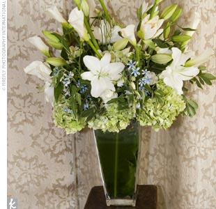 A single large arrangement of variegated Aspidistra leaves in a clear glass vase served as the focal point at the altar of the chapel. The arrangement also included green and white calla lilies, artificial lotus flowers, green and white hydrangeas, and lisianthuses, accented with light blue tweedia.