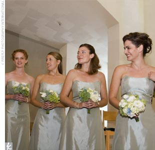 Althea's four bridesmaids perfectly personified the day's color scheme in silvery blue-colored tea-length satin-faced, taffeta dresses, the Empire waists accented by sage green bands, by Jim Hjelm Occasions.