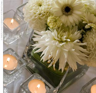 Two different types of centerpieces split among the tables created visual variety in the reception space. One was a square glass vase wrapped with greenery and filled with white dahlias and gerbera daisies.