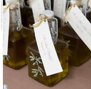 The mother of the bride and a few of her friends created the wedding favors. They hand-painted glass jars with Meagan's and Jake's names, wedding date, and their olive branch logo, then filled each with extra-virgin olive oil. The favors also had tags attached to serve as escort cards.