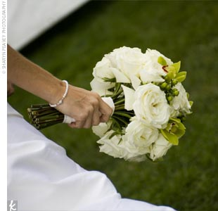 Reflecting the all-white, natural theme of the wedding, Jeannette's bouquet was bundled with white roses, green cymbidium orchids, and hypericum berries.