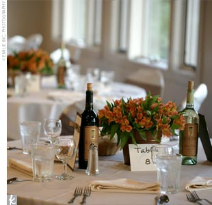 The tables were draped with ivory linens and every chair was wrapped with a chocolate-brown sash. Each table boasted an orange Amaryllis in a brown galvanized bucket surrounded by the couple's favorite red and white wines.