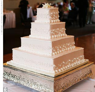"Amber and John cut a four-tier pale-pink cake that was decorated to mimic the embroidery in the bride's veil. Each tier featured a different flavor, including the bride's pick -- chocolate truffle. ""It was like eating a warm brownie!"" Amber says."