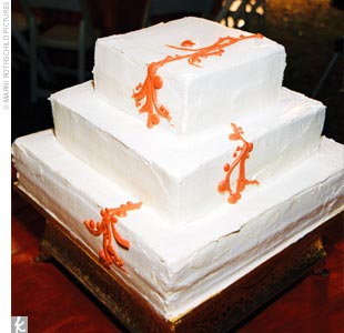 Naina and Dan cut a three-tiered white cake covered in cream cheese frosting.