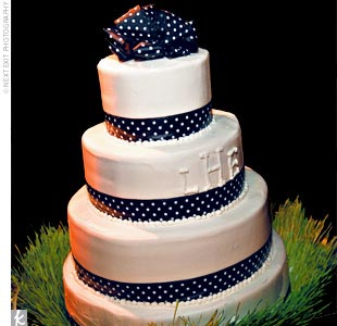 The four-tiered wedding cake was embellished with black-and-white polka-dot ribbon around each tier with a little bit of beading, and a monogram on one of the tiers. The chocolate mousse and carrot cake flavors were a hit with guests. Also, the cake and the place cards were set in flats of wheatgrass.