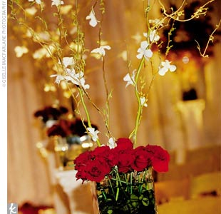 "The couple wanted floral arrangements that wouldn't overpower the dinner tables but would still be bold enough to add intimacy to the large space, so they chose red roses and curling willow with white orchids attached to the branches. ""Interestingly enough, we also had battery-operated candles due to the very restrictive fire code at Disney, and th ..."