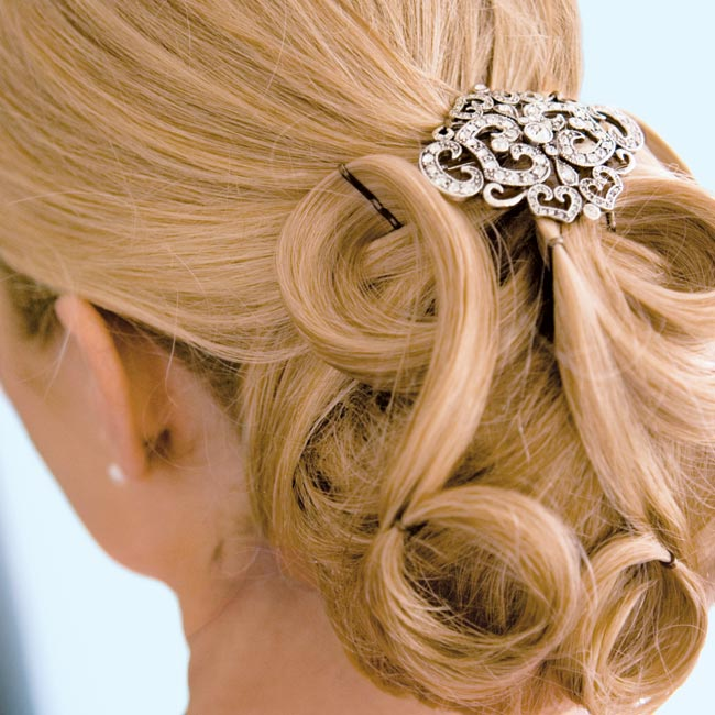 Jennifer's hair was pulled into a low bun in the back with a few light curls. She accessorized with a brooch.