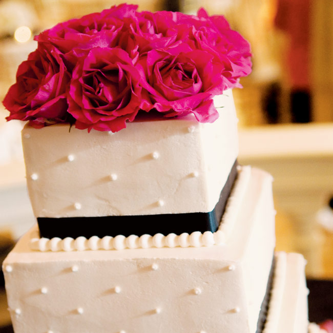 The cake, a four-tiered, square confection with alternating layers of fresh strawberries and lemon filling, was showcased at the reception. The stacked cake was decorated with white buttercream and a black ribbon of icing around the bottom of each tier. To finish it off, fuchsia roses, which matched the bridesmaid bouquets, added a pop of color to  ...