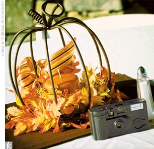 Jessica created the centerpieces herself. Each one was a metal pumpkin with an orange candle inside, surrounded by fall garland and a ribbon. The tables were set with brown placemats, the pumpkin centerpieces, and fall-hued leaves.