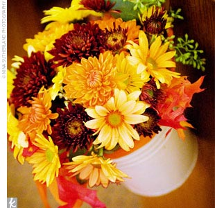 The eight reserved pews were lined with pails filled with a variety of fall-colored mums and tied with mango ribbons.
