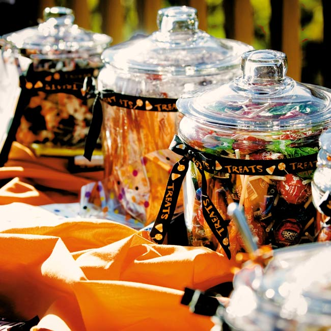 "Jessica found black, orange, and ivory polka-dotted fabric for the candy buffet table. Then she and her mother filled various-sized jars with their favorite Halloween candy, which included candy corn, Rolos, and candy apple lollipops. The jars were wrapped with a ribbon that read ""Trick or Treat!"""