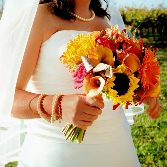 Jessica knew one thing for certain when it came to her flowers: they would be fall colors. Jessica carried a bouquet of mango calla lilies, red roses, small sunflowers, and orange gerbera daisies and added red berries for detail. The bouquet was wrapped with alternating mango and chocolate-brown ribbon.