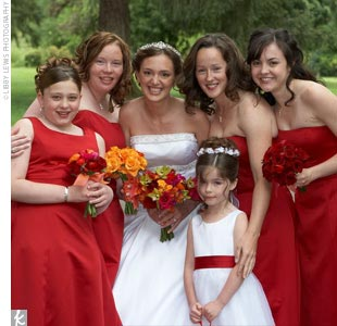 Courtney's three bridesmaids each wore a candy apple red cocktail dress with a small rhinestone decoration at the waist. Her junior bridesmaid wore the same dress in a longer version that also had shoulder straps.