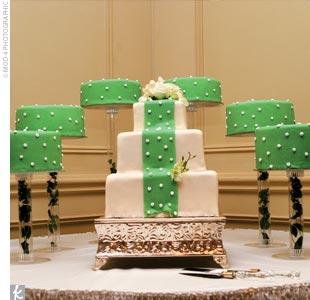 The couple's creativity met its match in their wedding cake designer, Patricia Ivery. Guests were treated to not just one clever cake (featuring the green and white polka-dot ribbon motif, of course) but also six satellite cakes frosted in green with white dots. Four cake flavors were on offer: banana cake with vanilla creme brulee and pralines, pi ...