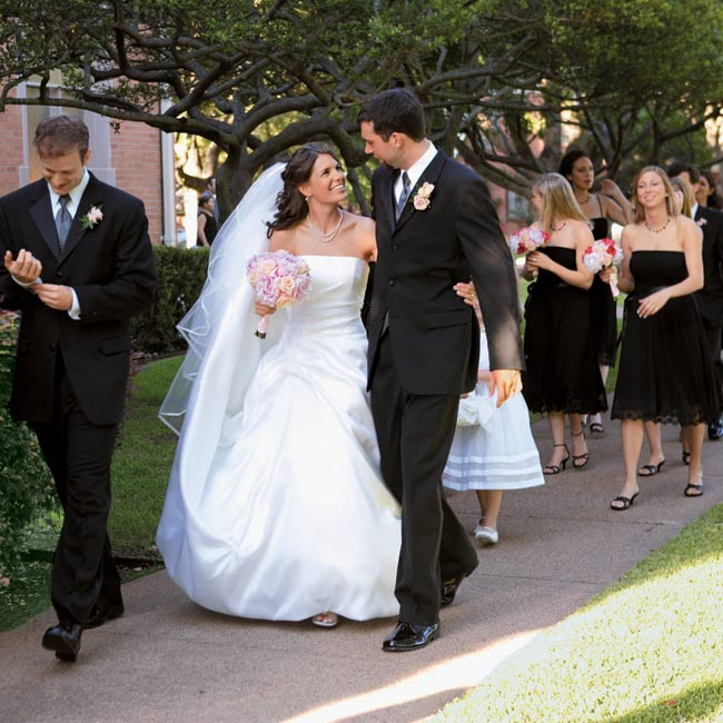 The color scheme was shown off best in the attire. The guys wore classic three-button tuxes, and for her eleven bridesmaids Ashley chose black dresses with pleated skirts that were finished off with lace at the hem. The bride herself wore a silk Mikado, A-line gown with a pick-up skirt by Eugenia Couture and carried a bouquet of pale pink roses and ...