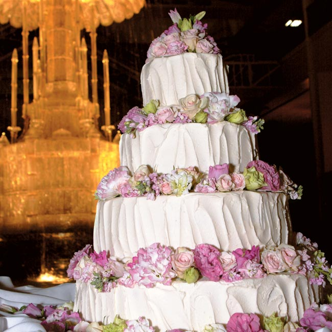 The wedding cake was a pink and white extravaganza, with four tiers covered in buttercream and topped with fresh pink flowers including spray roses, lisianthus, stock, and campanula. The same baker who had created Ashley's parents' wedding cake made this cake, and the couple even chose the same flavors—amaretto and Frangelico fillings in classic wh ...