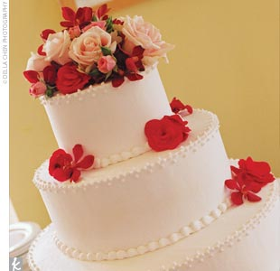 Angela and Peter cut into a three-tiered, stacked cake in a soft ivory color with delicate, frosted beading around the top edges. The cake itself was champagne-flavored and featured a different filling in each tier: champagne, lemon-chiffon, and raspberry. The confection was topped off with bright red and pink fresh flowers.