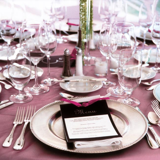Twenty round tables were dressed in white with fuchsia organza overlays, silver chargers, and white napkins.