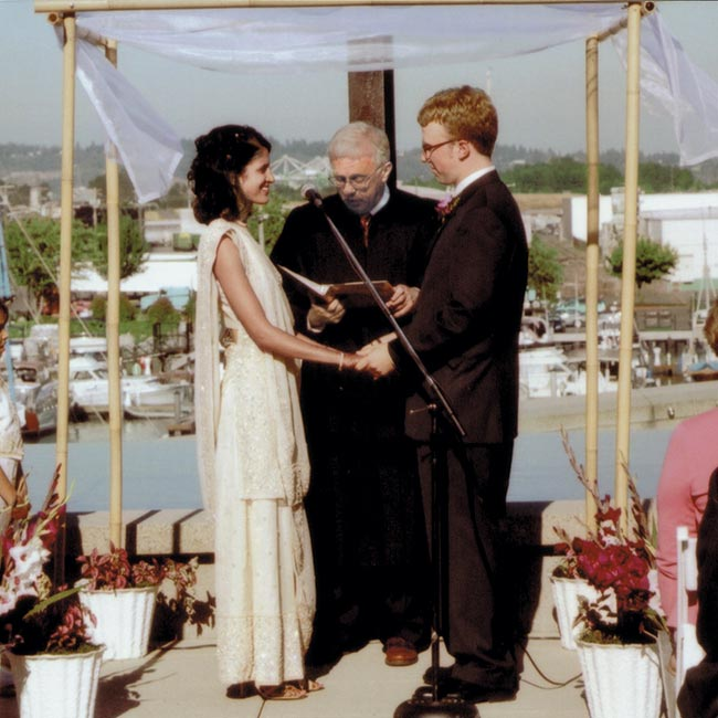 "The couple held their ceremony on the middle plaza in front of a reflecting pool, with views of the pool and the harbor beyond. Single dahlias floated in the water around them, and the bride and groom stood under a simple canopy made from bamboo and draped with gauzy fabric. The groom's father, a Spokane County Superior Court judge, officiated, ""wh ..."