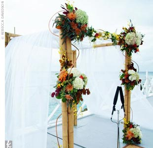 In true seaside style, the couple wed on a deck at the Grand Old House. The aisle was made of bamboo mats and lined with vases, complete with colored stones and candles. Amidst a variety of flowers and fall foliage, the couple stood beneath a bamboo canopy, woven with chiffon.  A special salt ceremony incorporated both of their mothers, joining the ...