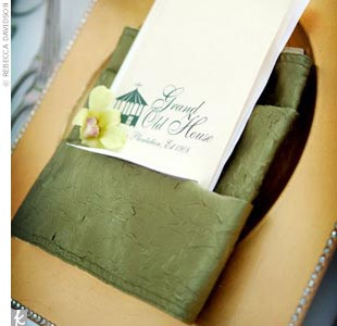 The seating cards and menu placed on each gold charger balanced the sage green tablecloth and flower centerpieces.