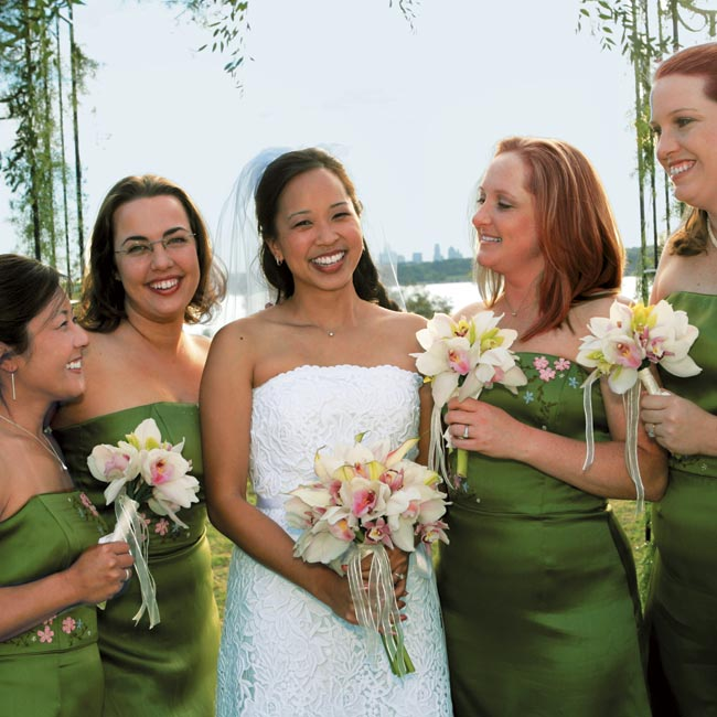 Melissa wore a strapless, tea-length gown of guipure lace that featured a white grosgrain sash and tulle peeking out at the hem. The bridesmaids wore silk satin organza, cocktail-length dresses in bright green with delicate blue and pink floral embroidery by Watters & Watters.