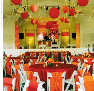 The reception that took place inside the main building was ablaze with color. Overhead, strings of Christmas lights and Chinese paper lanterns in red, pink, and orange created a warm glow, and giant-size orange and red lanterns stood around the room. Behind the DJ's stage were more lanterns, as well as large orange and red glass panels. The ivory-c ...