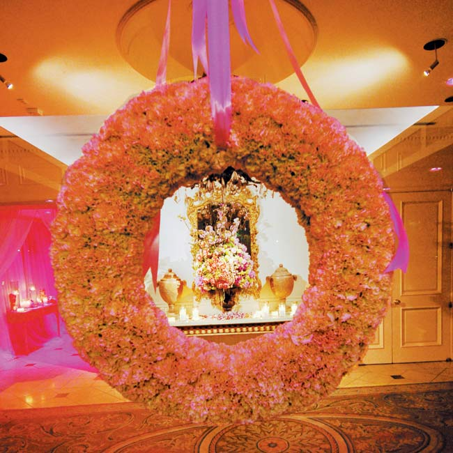 The cheerful color scheme was in full effect at the reception, held at the Dallas Country Club. As guests arrived, the main entrance was awash in pink light, and a wreath of green carnations hung in the front window.