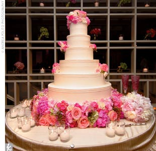 The brides cake was a six-tier round, white-chocolate cake with Italian cream filling and vanilla buttercream frosting. Pink and green hydrangea and pink and champagne-color roses cascaded down the side of the cake and wrapped around the base.