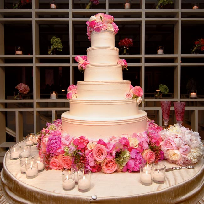 The bride's cake was a six-tier round, white-chocolate cake with Italian cream filling and vanilla buttercream frosting. Pink and green hydrangea and pink and champagne-color roses cascaded down the side of the cake and wrapped around the base.