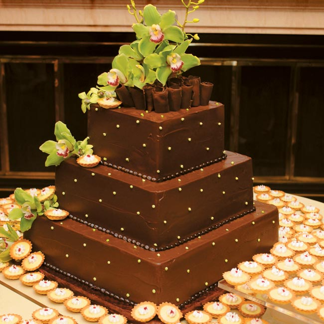 Kyle's groom's cake was the perfect complement: a three-tier square, chocolate fudge cake frosted in chocolate ganache–coated buttercream. A cascade of green cymbidium orchids provided a burst of color, as did the key lime pie tartlets (the groom's favorite dessert) that covered the cake table.
