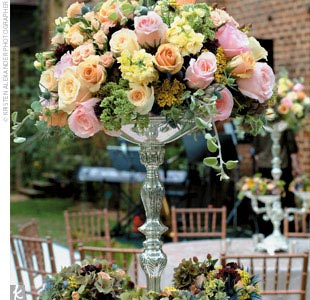 In the reception area, long, inviting tables were topped with the planters and flowers used during the ceremony, along with a few antique-style silver holders filled with more lush flowers.