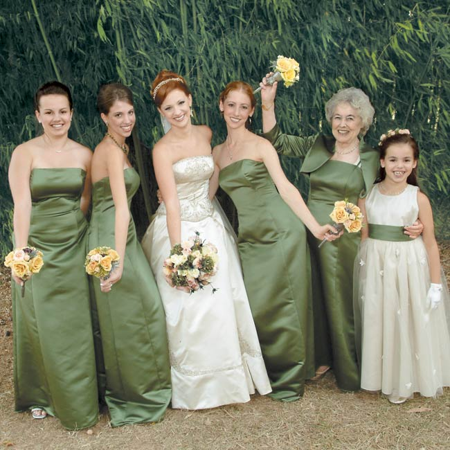 Fitting her wedding's enchanted theme, Leslie wore a strapless, pale gold ball gown with copper embroidery and a matching veil by Reem Acra. Leslie's bridesmaids wore strapless, dark green, long, A-line dresses with pleating on the skirts and a small train by Watters & Watters.