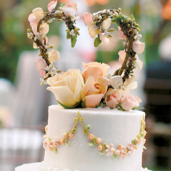 "In keeping with the wedding colors, the four-tiered cake was iced with ivory, peach, and green-color buttercream and decorated with the couple's monogram and a floral swag design inspired by the embroidered swag on Leslie's gown. The yellow pound cake was filled with almond marzipan filling. ""Almonds are good luck,"" says Leslie."