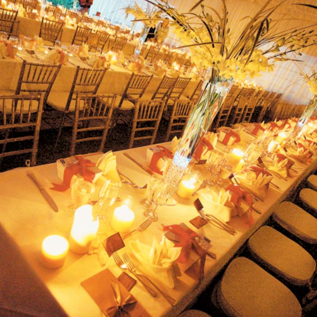"For the reception, four long banquet tables, which seated 16 guests on each side, were set up beneath a tent filled with candlelight. ""To me, long tables illustrate the togetherness and unity of family and friends,"" says Cybil. Centerpieces consisted of tall glass vases filled with orchids and Florida bear grass."