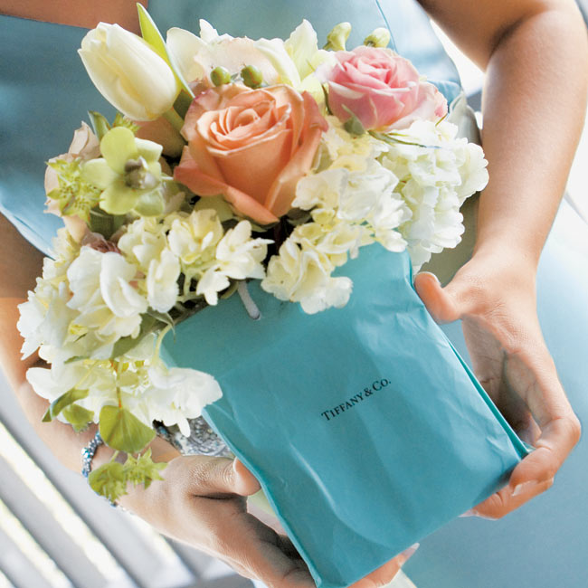 The bride's six bridesmaids pulled in the color theme most prominently with their bouquets: An assortment of coral pink roses, hydrangea, viburnum, lady's mantle, and ivy were tucked inside Tiffany & Co. handbags, which matched the iridescent, aqua blue, floor-length dresses.