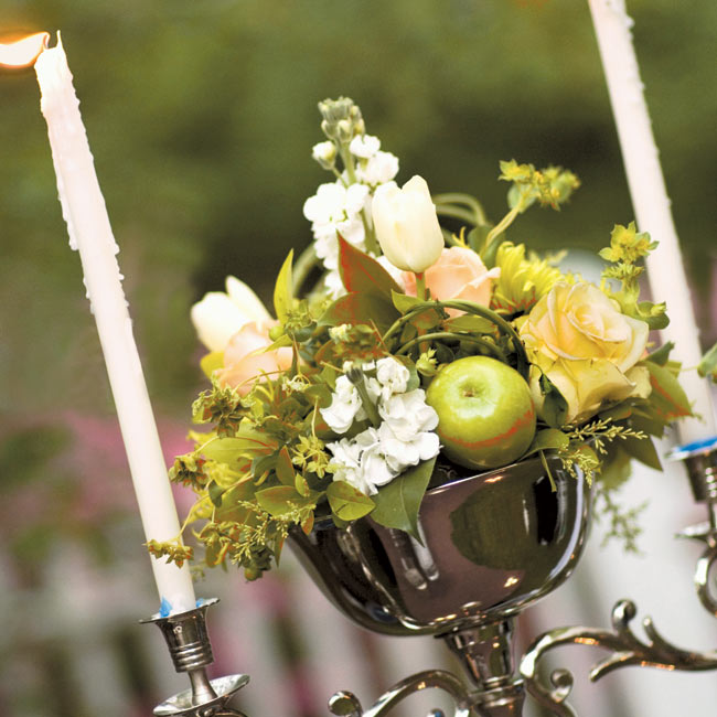 Silver bowls and silver baskets filled with apples, berries, and a mixture of roses, lady's mantle, and hydrangeas served as centerpieces.