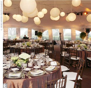 Round white lanterns glowed overhead at the tented reception, while tables draped in copper-colored linens surrounded the dance floor.