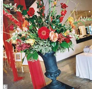 To stand out against the stark space of the gallery, Lisa and Will chose an eye-popping palette of red and orange. They also figured these hues would be perfect for the flowers -- a vivid contrast with green leaves.