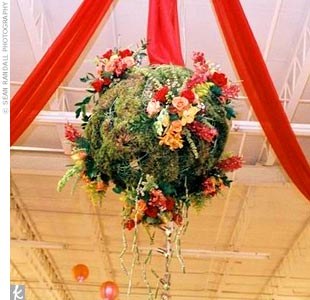 "As guests entered the gallery, they walked along a hallway accented by draped red fabric where Lisa and Will's collages and the mother of the groom's artwork were on display. The drapes then flowed up and were gathered with a ""flower ball"" of grape vines, moss, curly willow, and bamboo hanging above the cake."